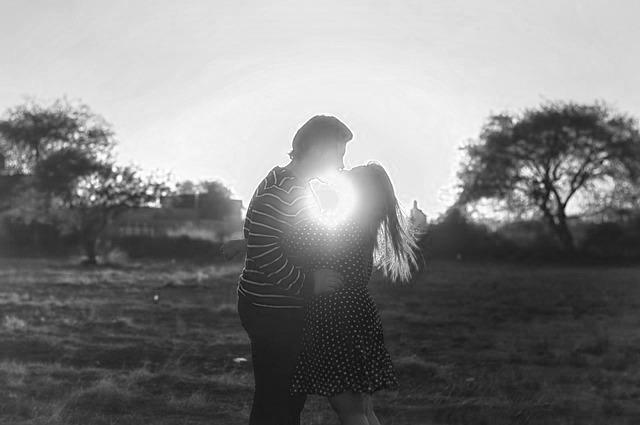 夕日をバックにキスするカップル ハグ