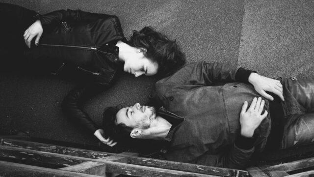 道に寝転がるカップル 見つめ合う