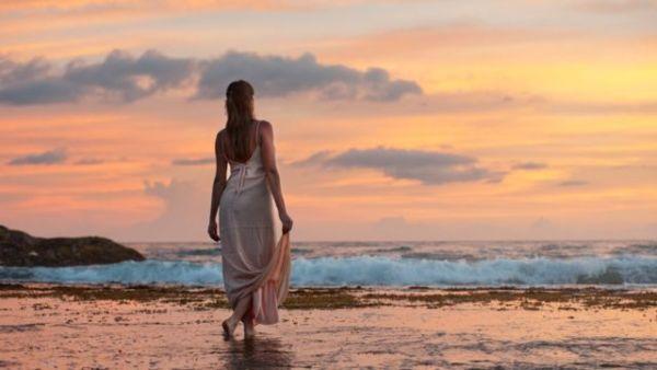 海辺で黄昏れる女性 夕日