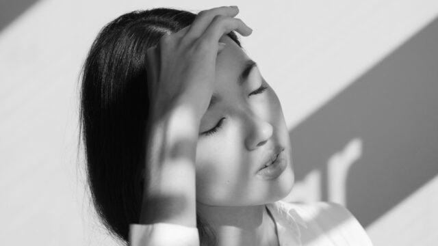 額を押さえる女性 頭痛 偏頭痛 発熱